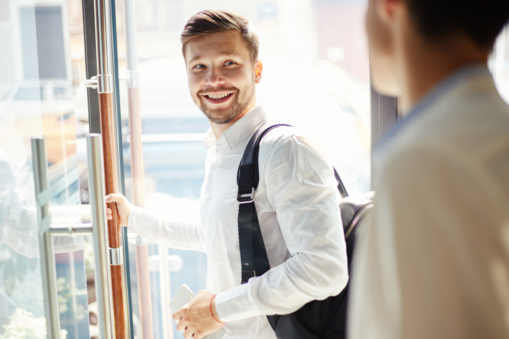uśwmiechnięty mężczyzna wbiałej koszuli otwiera szklane drzwi ipatrzy się nainnego mężczyznę
