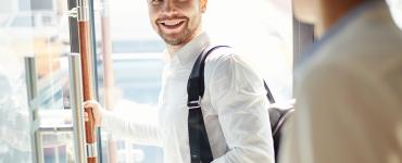 uśwmiechnięty mężczyzna w białej koszuli otwiera szklane drzwi i patrzy się na innego mężczyznę