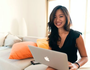 Uśmiechnięta kobieta siedząca z laptopem na kanapie
