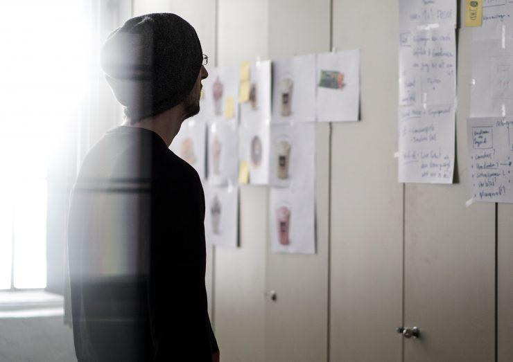 mężczyzna w czapce patrzy na zadania na kartkach przyczepionych do szafy