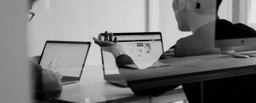 dwie osoby rozmawiające przy biurku i laptopach fotografia czarno-biała