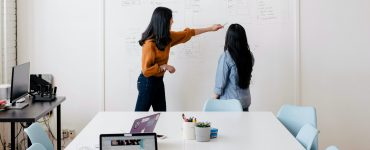 a young dark-haired woman in an office spaice indicating a point on a whiteboard to a shorter dark-haired woman