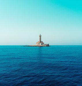 latarnia morska na tle błękitnego nieba i granatowego morza