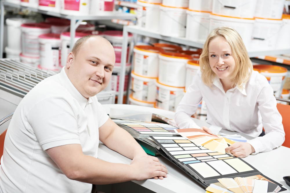 Man worker and woman client in a retail paint shop choose a color of a paint