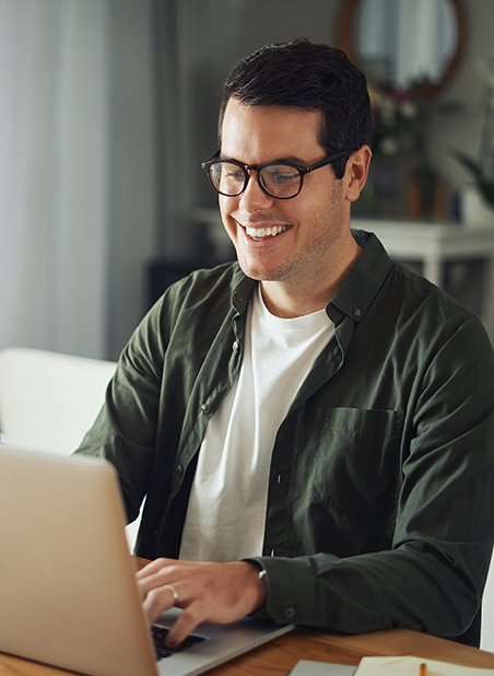 Brunet man with glasses looking at a laptop's monitor smiling at home