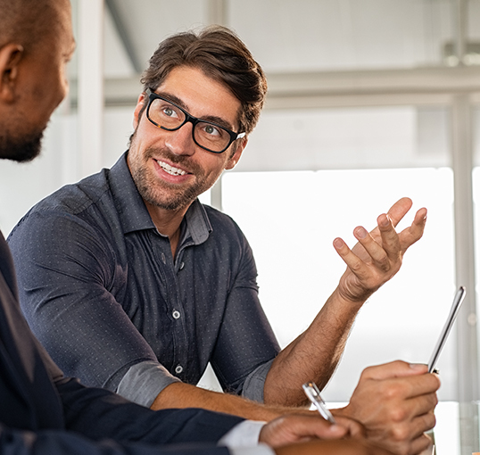 Young bearded man with glasses explains something to another man with a positive attitude
