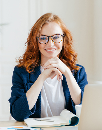 red-headed pale skin woman with glasses and curly hair siitting in front of a silver laptop looking at the camera smiling
